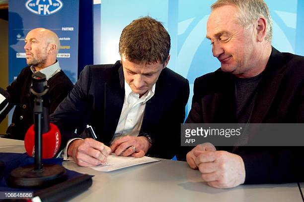 Ole Gunnar Solskjaer is watched by chairman Erik Berg of Molde FK as he signs a contract during a press conference in Molde on November 9 2010 where...