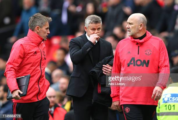 Ole Gunnar Solskjaer, Manager of Manchester United and coaches Mike Phelan and Kieran McKenna in discussion at half time during the Premier League...