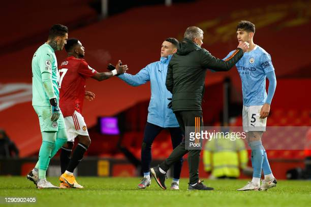 Ole Gunnar Solskjaer, Manager of Manchester United and Fred shake hands with Ederson, John Stones and Phil Foden of Manchester City after the Premier...