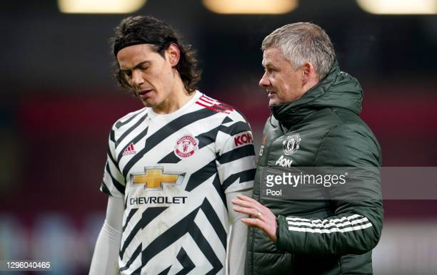 Ole Gunnar Solskjaer, Manager of Manchester United speaks to Edinson Cavani of Manchester United as they walk off at half time during the Premier...
