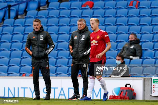 Ole Gunnar Solskjaer, Manager of Manchester United speaks with Donny Van De Beek of Manchester United as he prepares to be substituted on during the...