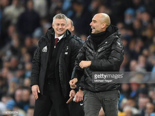 Ole Gunnar Solskjaer Manager of Manchester United speaks with Pep Guardiola Manager of Manchester City during the Premier League match between...