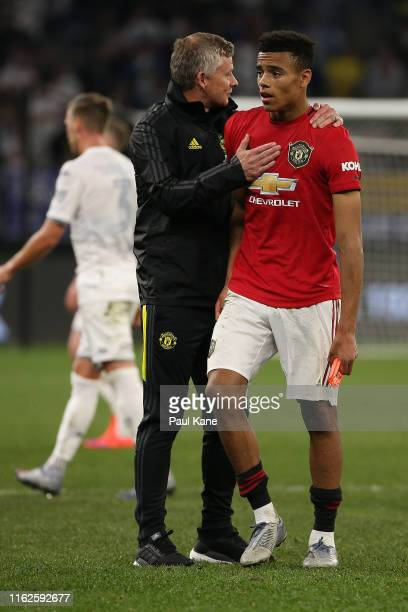 Ole Gunnar Solskjaer manager of Manchester United talks with Mason Greenwood as players walk from the field at half time during a preseason friendly...