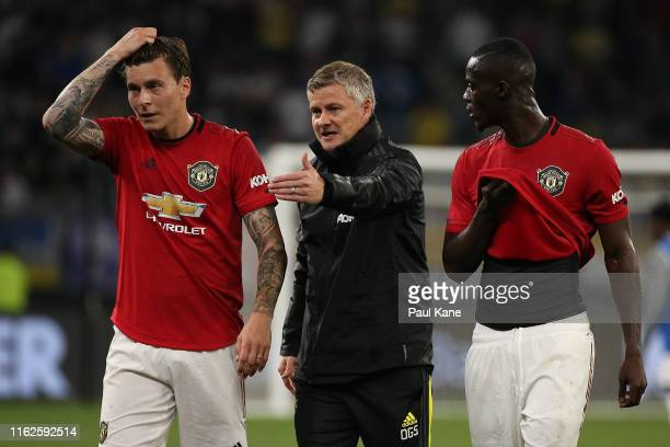Ole Gunnar Solskjaer manager of Manchester United talks with Victor Lindelof and Eric Bailly as players walk from the field at half time during a...