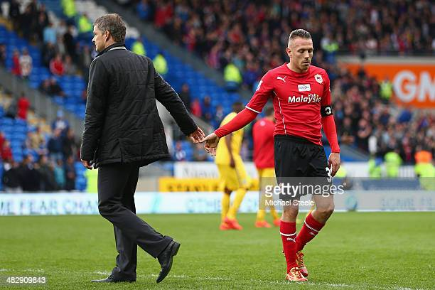 Ole Gunnar Solskjaer the manager of Cardiff City shakes the hand of Craig Bellamy at the final whistle after their 03 defeat during the Barclays...