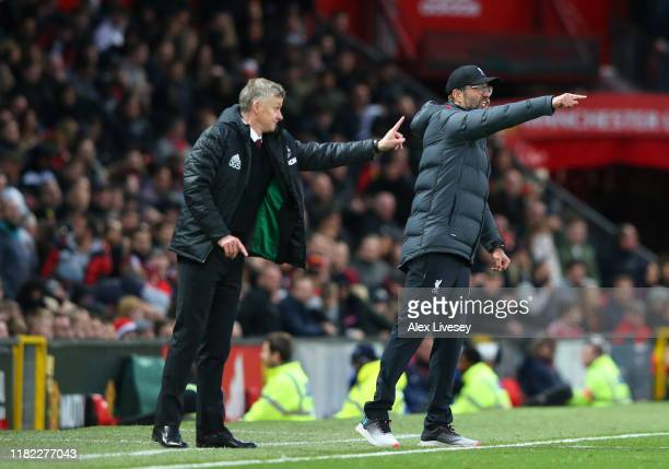 Ole Gunnar Solskjær Manager of Manchester United and Jurgen Klopp Manager of Liverpool gives their side instructions during the Premier League match...