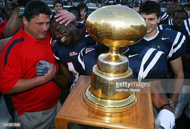 Ole Miss head coach Ed Orgeron hugs linebacker Patrick Willis while the team accepts the Egg Bowl trophy after defeating Mississippi State at...