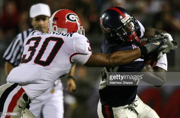 Ole Miss running back Mico McSwain protects the ball against Georgia free safety Kelin Johnson at Vaught-Hemingway Stadium in Oxford, Miss. On...