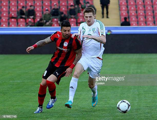 Oleg Ivanov of FC Terek Grozny is challenged by Blagoy Georgiev of FC Amkar Perm during the Russian Premier League match between FC Terek Grozny and...