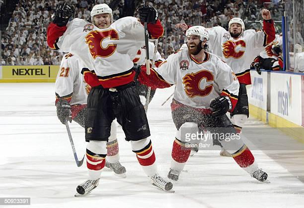 Oleg Saprykin Chris Clark and Chris Simon of the Calgary Flames celebrate Saprykin's game winning goal in overtime against the Tampa Bay Lightning in...