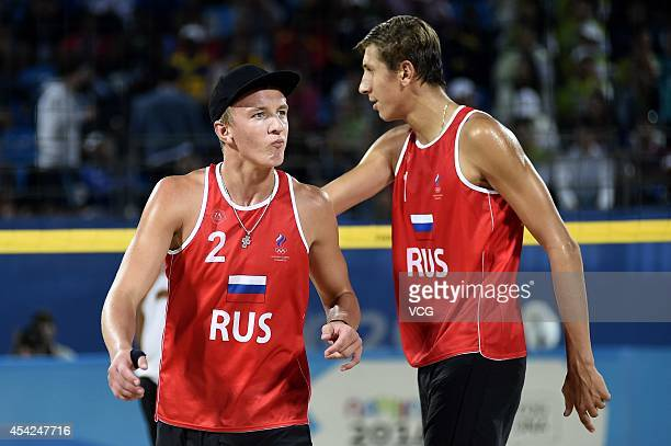 Oleg Stoyanovskiy and Artem Larzutkin of Russia compete with Jose Gregorio Gomez and Rolando Hernandez of Venezuela in the Men's Beach Volleyball...