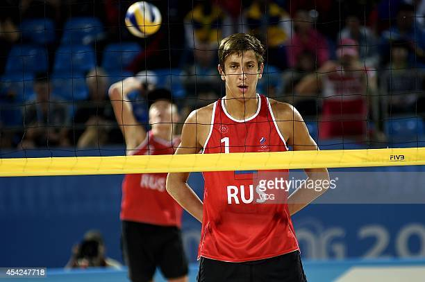 Oleg Stoyanovskiy of Russia competes with Rolando Hernandez and Jose Gregorio Gomez of Venezuela in the Men's Beach Volleyball Final match on day...