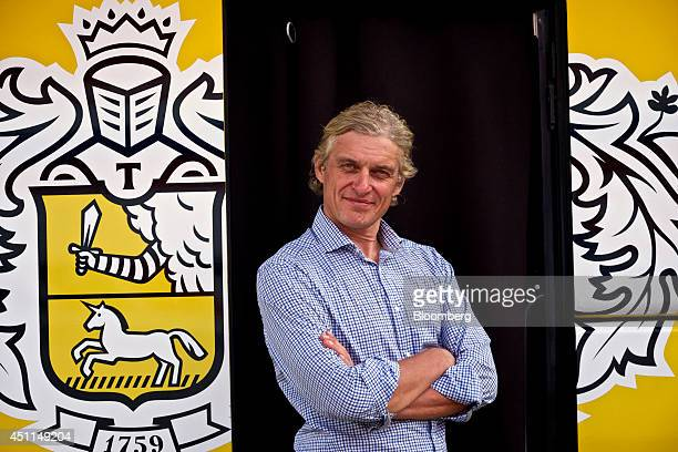 Oleg Tinkov a Russian millionaire and founder of TCS Group Holding Plc poses for a photograph standing alongside the TinkoffSaxo race bus after...