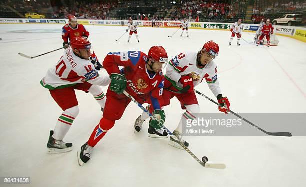 Oleg Tverdovsky of Russia is sandwiched by Oleg Antonenko and Viktor Kostiuchenok of Belarus during the IIHF World Championship Quarter-Final between...