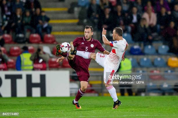 Olegs Laizans of Latvia competes with Xherdan Shaqiri of Switzerland during the FIFA 2018 World Cup Qualifier between Latvia and Switzerland at...