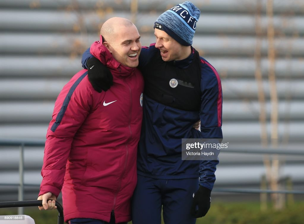 Oleksandar Zinchenko and coach Barry Hamilton joke during training at Manchester City Football Academy on December 12, 2017 in Manchester, England.