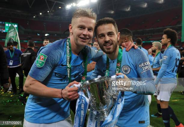 Oleksandr Zinchenko and Bernardo Silva of Manchester City celebrate victory with the trophy after the Carabao Cup Final between Chelsea and...