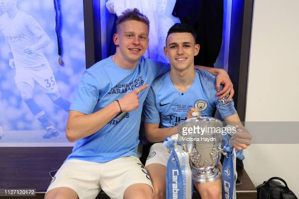 Oleksandr Zinchenko and Phil Foden of Manchester City pose with the trophy after winning the Carabao Cup Final between Chelsea and Manchester City at...