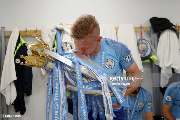 Oleksandr Zinchenko of Manchester City celebrates with the Premier League Trophy after winning the title following the Premier League match between...