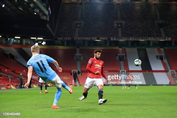 Oleksandr Zinchenko of Manchester City clears past Bruno Fernandes of Manchester United during the Carabao Cup Semi Final match between Manchester...