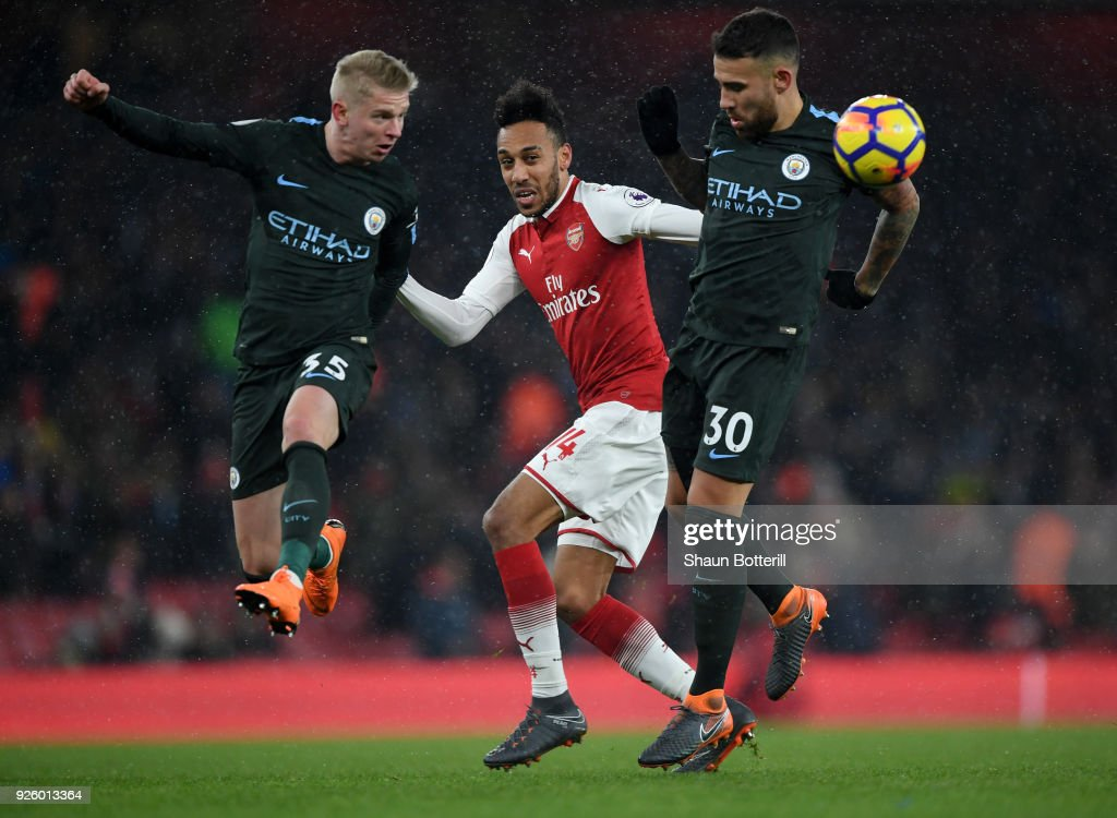 Oleksandr Zinchenko (l) of Manchester City heads the ball clear of Pierre-Emerick Aubameyang of Arsenal alongside Nicolas Otamendi (r) during the Premier League match between Arsenal and Manchester City at Emirates Stadium on March 1, 2018 in London, England.