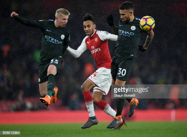 Oleksandr Zinchenko of Manchester City heads the ball clear of PierreEmerick Aubameyang of Arsenal alongside Nicolas Otamendi during the Premier...