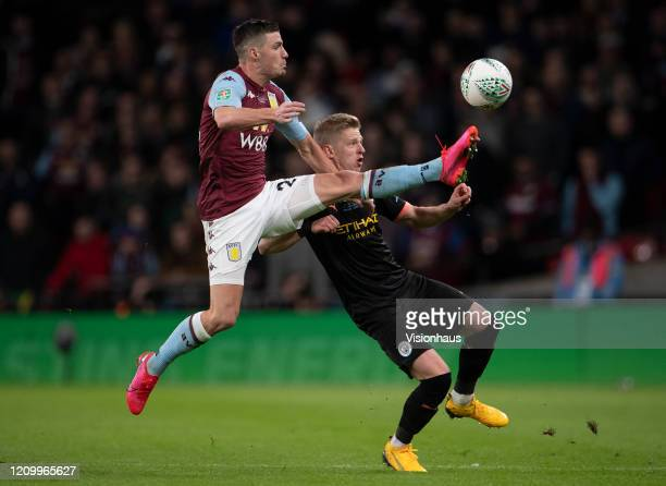 Oleksandr Zinchenko of Manchester City is beaten to the ball by Frédéric Guilbert of Aston Villa during the Carabao Cup Final between Aston Villa and...