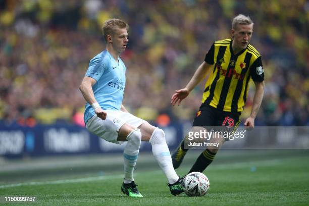 Oleksandr Zinchenko of Manchester City passes the ball under pressure from Will Hughes of Watford during the FA Cup Final match between Manchester...