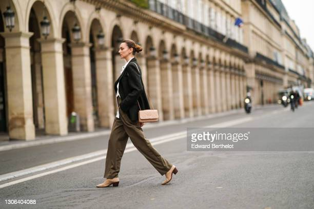 Olesya Senchenko wears a green wool oversize blazer jacket, a white long shirt, khaki pants, a pink quilted Chanel leather bag, beige pointy boots...