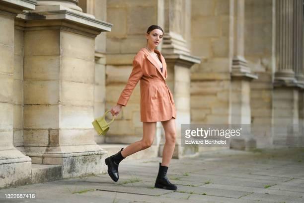 Olesya Senchenko wears a white pearls necklace, a gold chain necklace, earrings, a pale orange blazer jacket oversized dress, a black bra underwear,...