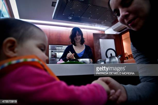 Olga cooks as Matilde feeds their daughter Carolina at their home in Odivelas outskirts of Lisbon on February 19 2014 Matilde Custodio 35 years old...