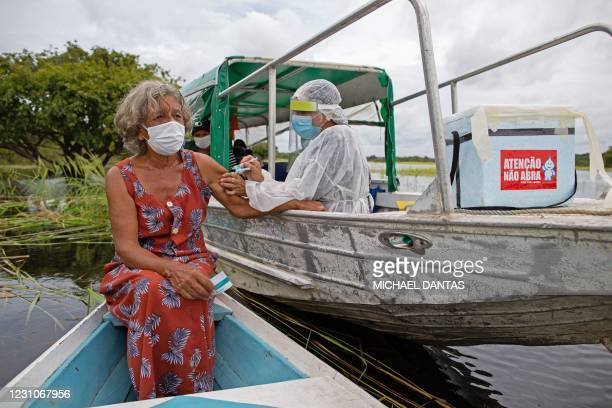 Olga D'arc Pimentel is vaccinated by a health worker with a dose of Oxford-AstraZeneca COVID-19 vaccine in the Nossa Senhora Livramento community on...