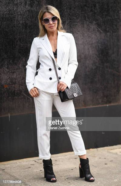 Olga Ferrara is seen wearing a striped suit with a Chanel bag outside the Studio 189 show during New York Fashion Week S/S21 on September 16, 2020 in...