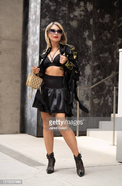 Olga Ferrara wears Callista by Vinta earrings, black and gold Videmus Omnia Jacket, black skirt and a St. Jonhs bag with black leather boots on...