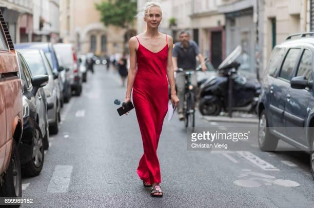 Olga Karput wearing a red silk dress outside Dries van Noten during Paris Fashion Week Menswear Spring/Summer 2018 on June 22 2017 in Paris France
