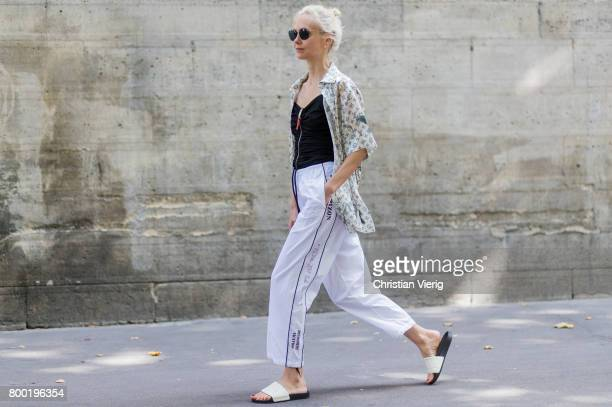 Olga Karput wearing white jogger pants Louis Vuitton button shirt outside Junya Watanabe Man during Paris Fashion Week Menswear Spring/Summer 2018 on...