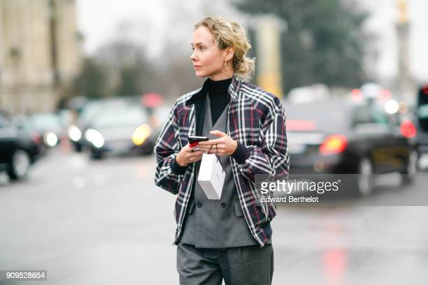 Olga Karput wears a checked jacket a gray blazer a gray suit holds a smartphone outside Chanel during Paris Fashion Week Haute Couture Spring/Summer...