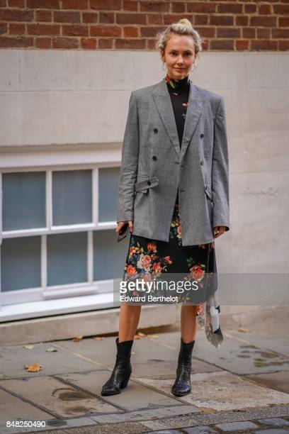 Olga Karput wears a gray blazer jacket a flower print dress black boots outside Simone Rocha during London Fashion Week September 2017 on September...