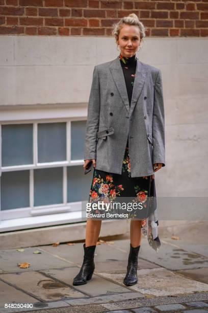 Olga Karput wears a gray blazer jacket a flower print dress black boots outside Simone Rocha during London Fashion Week September 2017 on September...
