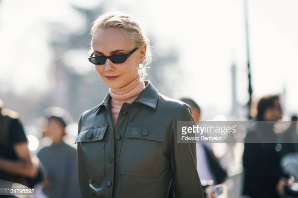 Olga Karput wears a pink turtleneck, a green leather coat, earrings, sunglasses, outside Maison Margiela, during Paris Fashion Week Womenswear...