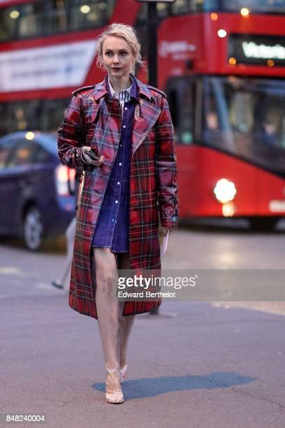Olga Karput wears a red gingham plastic rain coat white heels and a blue denim dress outside the Burberry show during London Fashion Week September...