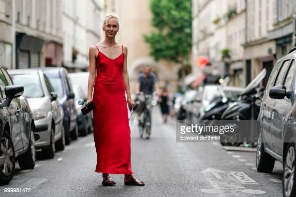 Olga Karput wears a red silk dress outside Dries van Noten during Paris Fashion Week Menswear Spring/Summer 2018 on June 22 2017 in Paris France