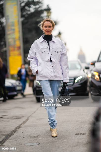 Olga Karput wears a turtleneck and a white jacket blue jeans during Paris Fashion Week Womenswear Fall/Winter 2018/2019 on March 1 2018 in Paris...