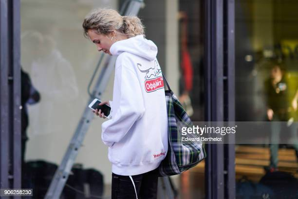 Olga Karput wears a white hoodie sweater a checked bag black leather pants outside Off White during Paris Fashion Week Menswear Fall Winter 20182019...