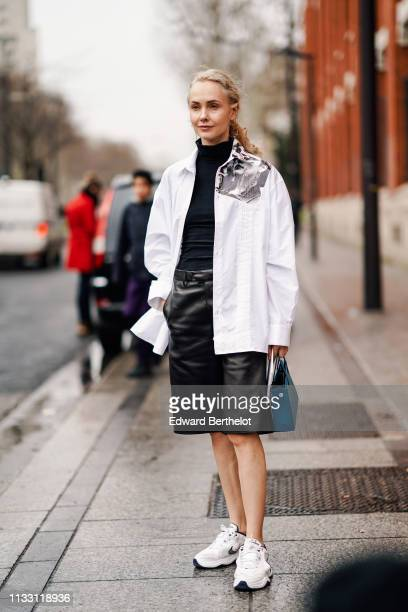 Olga Karput wears earrings a black turtleneck a white shirt with a black and white impression on the shoulder depicting piercings lustrous black...