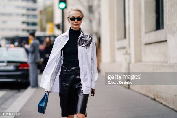 Olga Karput wears earrings sunglasses a black turtleneck a white shirt with a black and white impression on the shoulder depicting piercings lustrous...