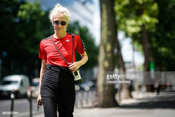 Olga Karput wears sunglasses a red top black pants sandals outside the Y3 show during Paris Fashion Week Menswear Spring/Summer 2018 on June 25 2017...