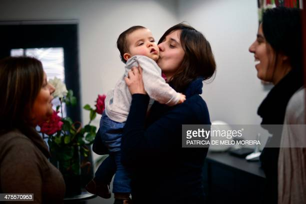 Olga kisses her daughter Carolina as partner Matilde and her mother Carolina's grandmother look on in their Odivelas home on February 21 2014 Matilde...