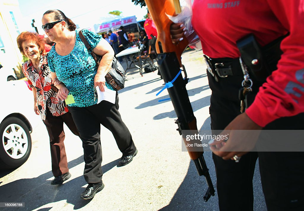 Olga Moran (L) and Azalea Moran walk together after turning in an AK-47 as the City of Miami police take in weapons during a gun buy back event on January 26, 2013 in Miami, Florida. The event was the second one of the year in efforts to reduce gun violence, the first one brought in 130 guns.