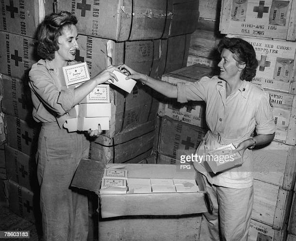 Olga Randolph and Barbara Chase pack cases of American Red Cross gift packages at the Dutch New Guinea base for distribution in hospitals on...